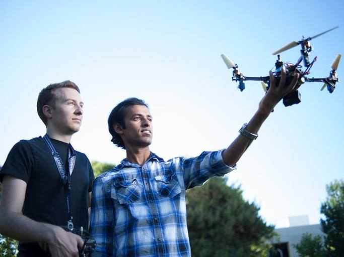 Two male students - one is holding a drone in his left hands