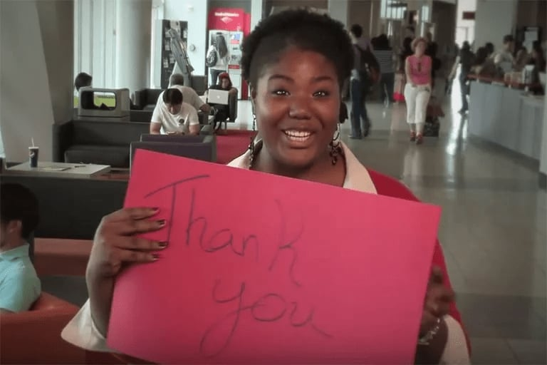 A woman in the Student Union holding up a red sign that reads thank you.