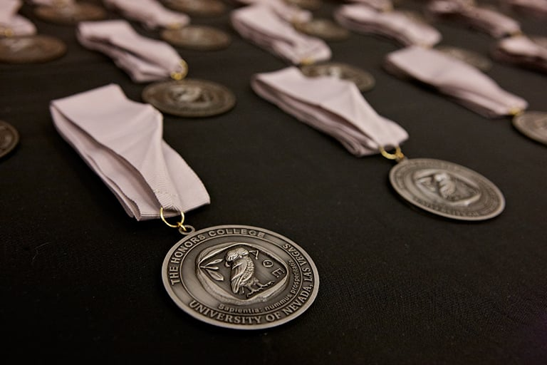 Honor Colleges medals lined up on a table