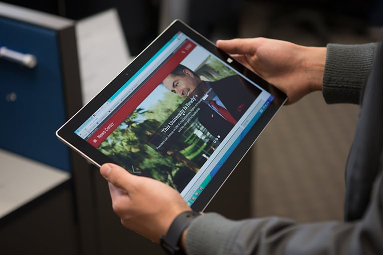 Hands holding a tablet that shows the U-N-L-V News Center on  the screen.