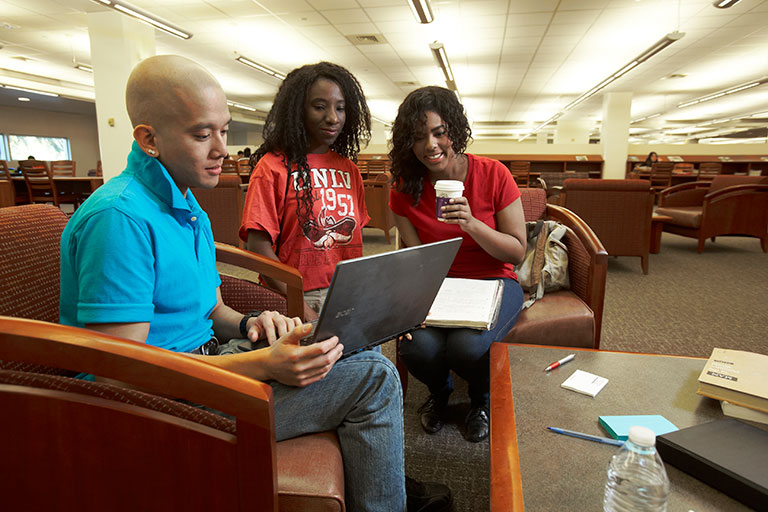 Three students sitting down at the library