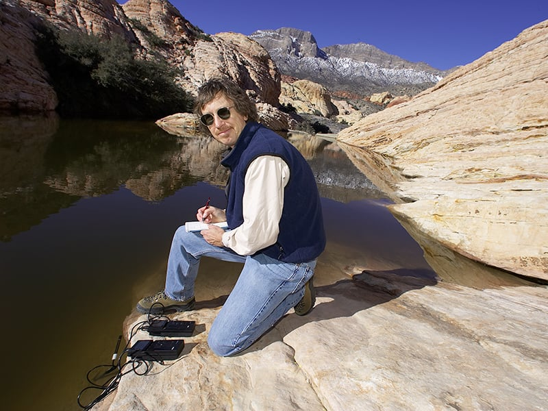 "alt=""Scientist doing testing at a lake."""