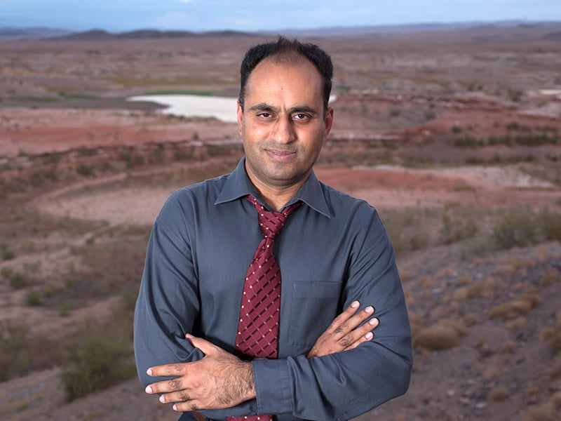 "alt=""Professor Ahmad with Lake Mead in the background at a very low water level."""