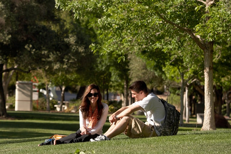 "alt=""Two students sitting on the grass"""