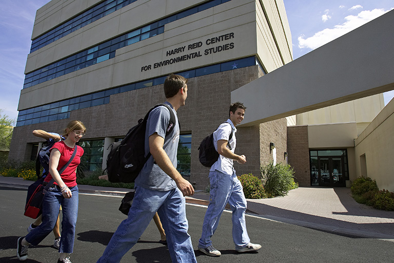 Students walking along the outside of the Harry Reid Center Building