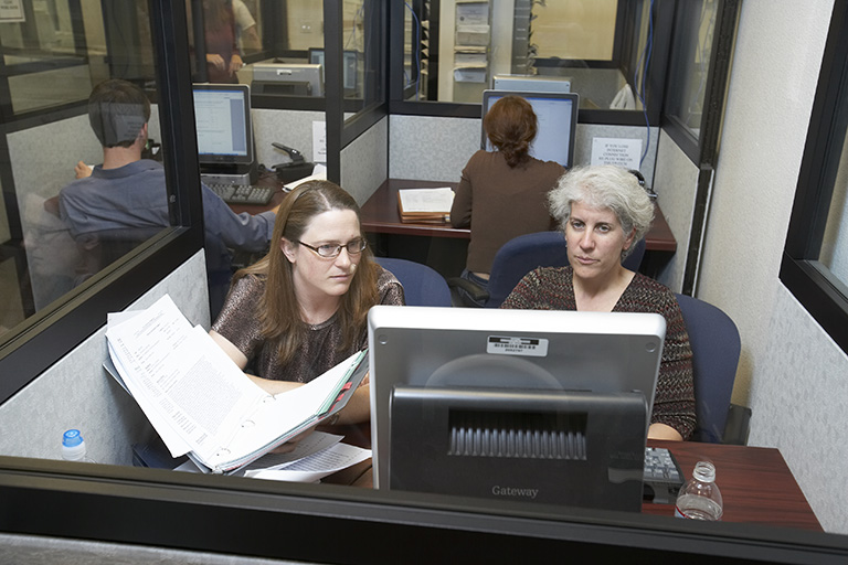 Two women working inside of a single cubicle