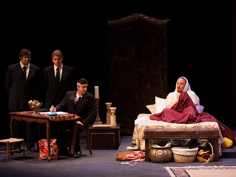 On a theatre stage there are three men in suits surrounding a small table next to a man wrapped in blankets on a bed