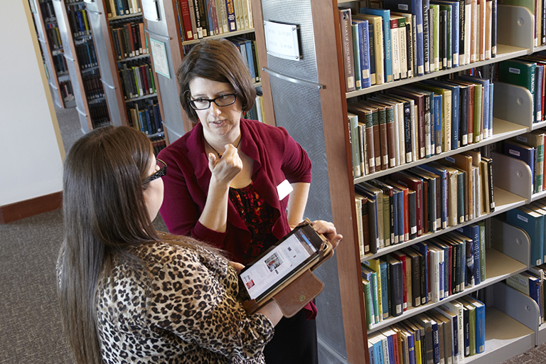 Two woman talking to each other inside of a library