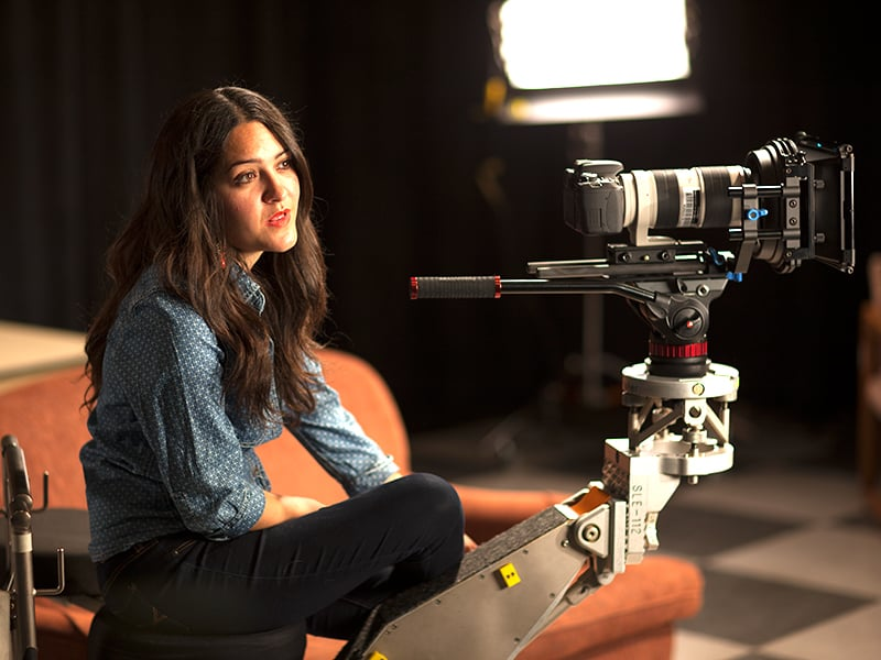 Female student sitting down behind a camera in a dimly lit room
