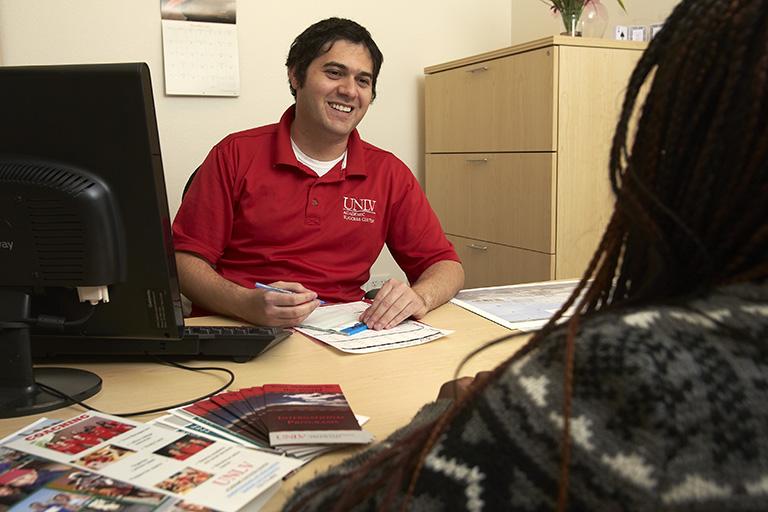 academic advisor helping student at office desk