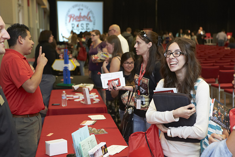 Students gathering around a table during a convention