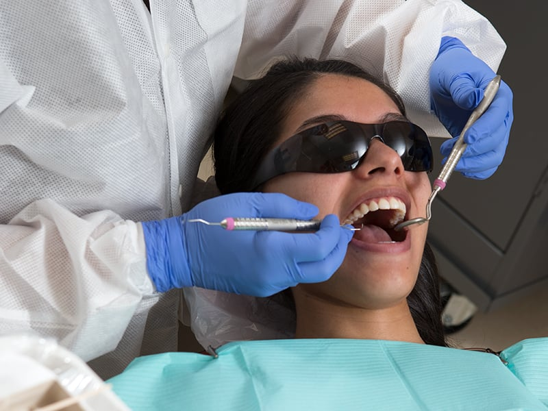 Patient having teeth cleaned at a Dental Clinic.