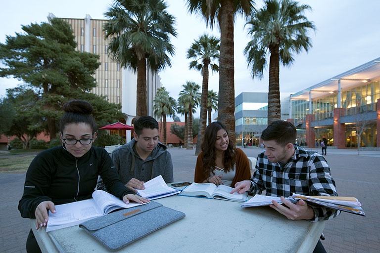 Students sitting at a table outside the student union.