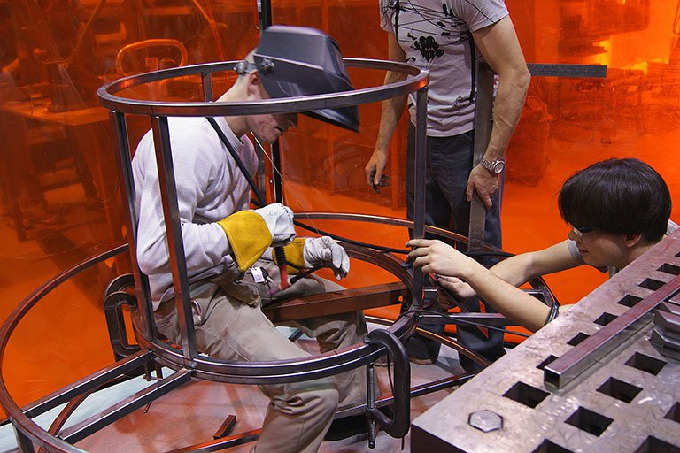 Three students working on a large metal structure
