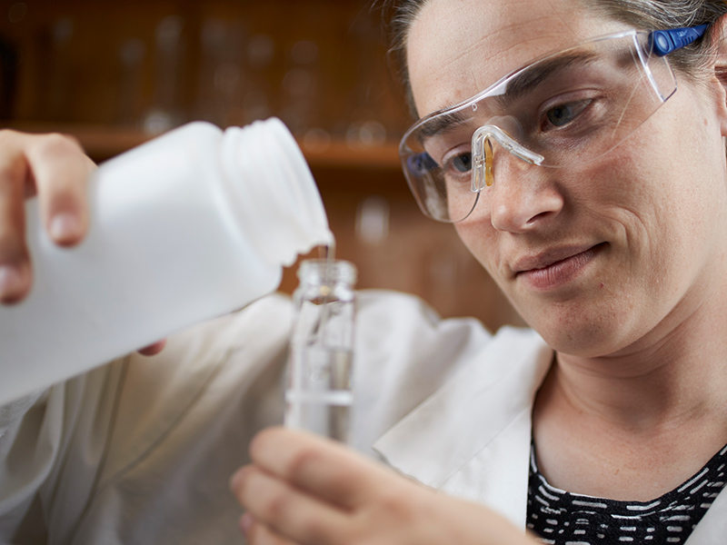 Researcher pouring liquid into a test tube