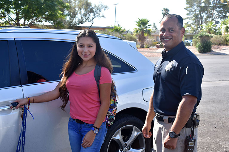 A girl and an officer next to a car
