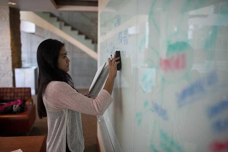 Person writing on a white board.