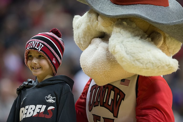 UNLV mascot Hey Reb posing for a picture with a young fan