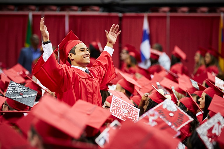 Student stands with hands in the air during commencement.