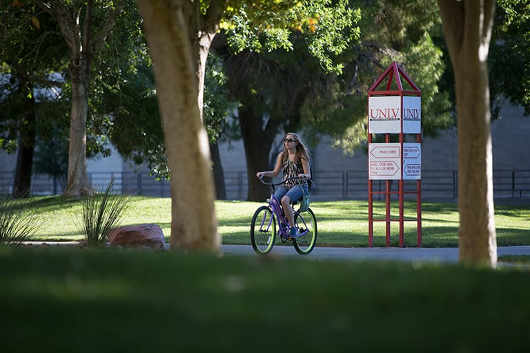 Girl riding her bike on campus.