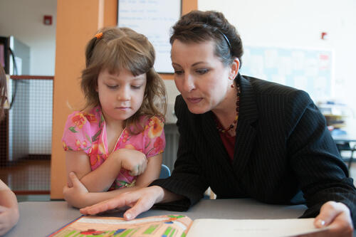 A teacher reading to an elementary school student