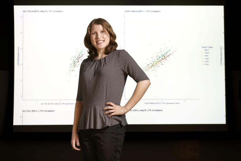 Sophia Quinton standing, hand on hips, in front of a screen with a graph