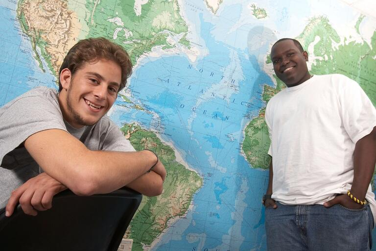 Two students pose in front of a world map
