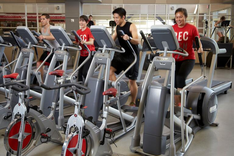 Four students use excercize bikes
