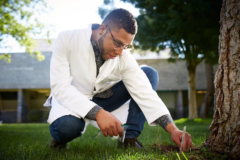 Man in lab coat crouching.