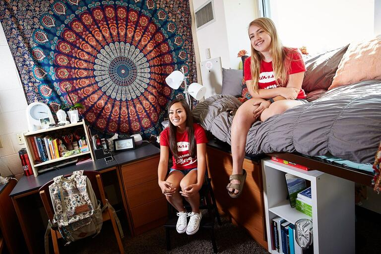 Two students sit in a their dorm room
