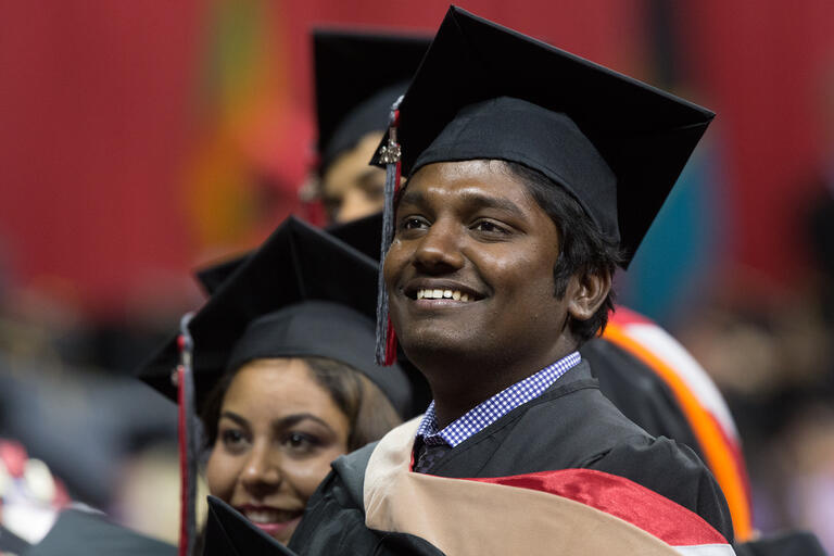 Graduate student smiling during Commencement